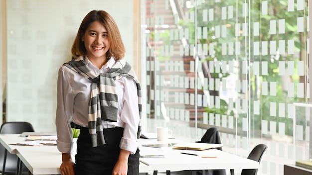 会議室で自信を持って笑顔の美しいアジア女性実業家。 Premium写真