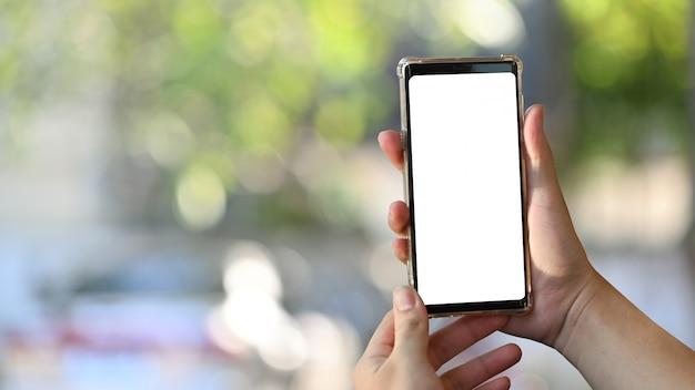 ぼやけている自然のボケ味でモバイルスマートフォンを保持しているクローズアップ男 Premium写真