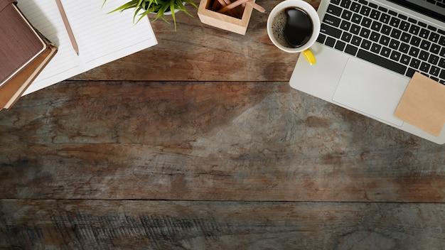 木製の机の上のノートパソコン、ノート、鉛筆、コーヒーカップのトップビュー Premium写真