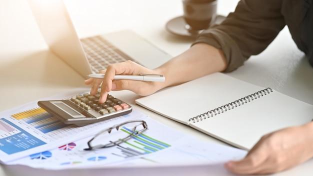 クローズアップ動機金融女性は、オフィスの机の上のデータを計算します。 Premium写真