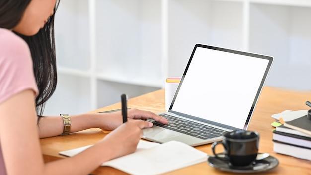 若い女性は、メモ用紙を読んで、図書室で孤立した白い画面のラップトップを使用しています。 Premium写真