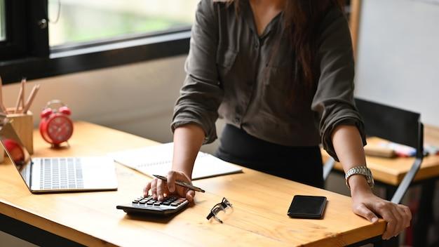 Подрезанная женщина выстрела вычисляет финансовое на калькуляторе. Premium Фотографии