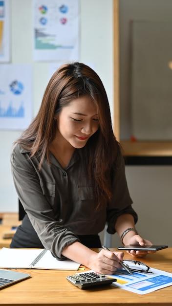 携帯電話を保持している書類の若い会計女性分析。 Premium写真