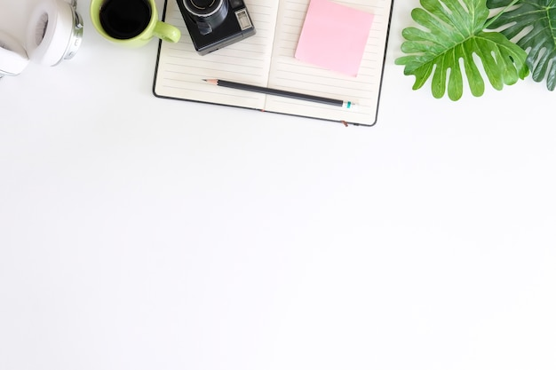 カメラ付きオフィスデスク、鉛筆、メモ帳、ワークスペースにコーヒー付きヘッドフォン Premium写真