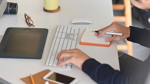 ワークデスクでの作業に集中しながら若い創造的な男のサイドショット。キーボード、マウス、ノート、ペン、スマートフォン、メガネ、カメラ、作業机の上。 Premium写真