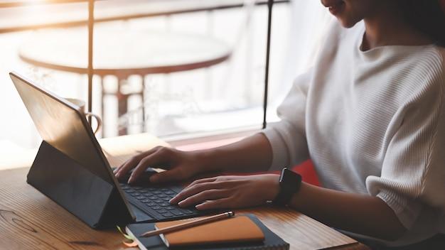 Обрезанное изображение красивой женщины, набрав на планшетном компьютере с клавиатурой, сидя за аккуратным деревянным столом над гостиной Premium Фотографии