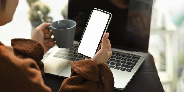 リビングルームの革のソファで彼女のラップトップの前に座っている間コーヒーカップと白い空白の画面のスマートフォンを保持しているクローズアップの女性。在宅勤務/リモートワーキングコンセプト。 Premium写真