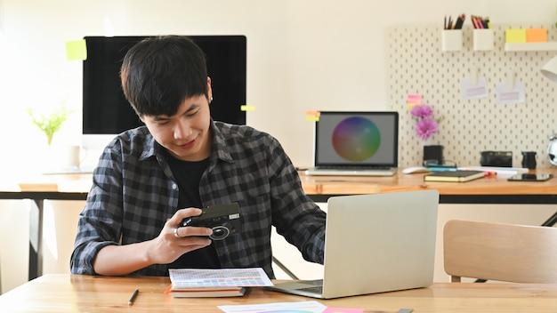 Молодой график-дизайнер работая его камера и компьтер-книжка в творческой студии. Premium Фотографии