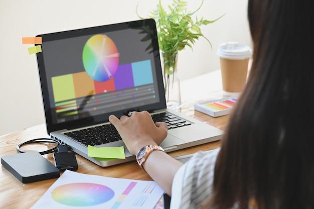 Графический дизайнер ее выбирая цвет с ноутбуком и креативные аксессуары на столе. Premium Фотографии