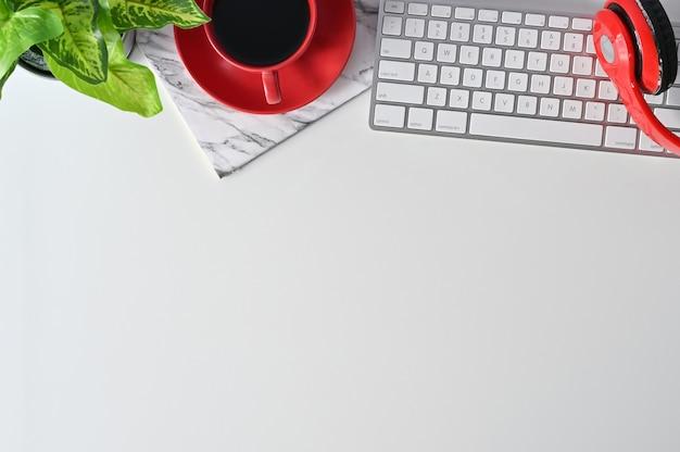 コンピューター、ヘッドフォン、鉛筆、コーヒー、植物の装飾が施されたオフィスデスクテーブルトップ。 Premium写真
