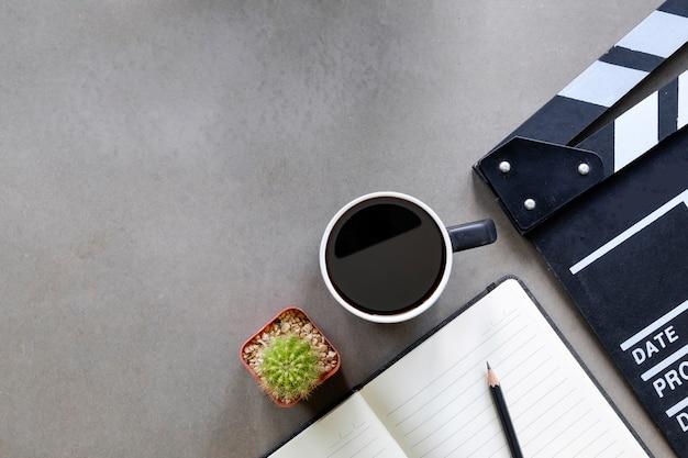 メモ帳の紙、一杯のコーヒー、監督テーブルトップビューとコピースペースにサボテンの映画クラッパー。 Premium写真