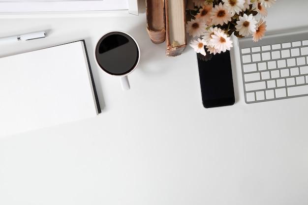 事務机のスマートフォンモックアップ、コーヒー、コンピューター、本、上面と白いテーブルの上の花。 Premium写真
