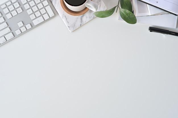 フラットレイアウト平面図事務机。キーボードと事務用品のあるワークスペース。 Premium写真