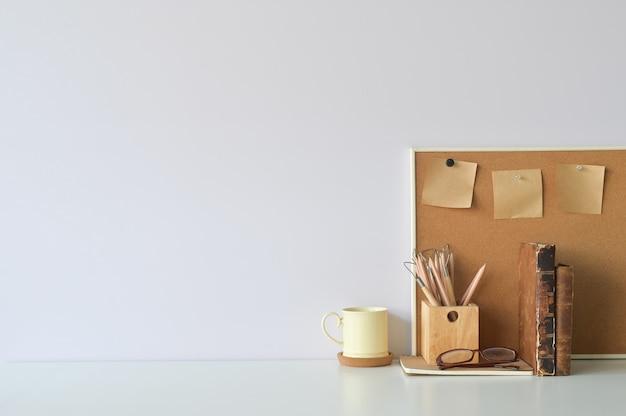オフィスのワークスペースのコーヒー、鉛筆、書籍、コピースペースを持つボード上の付箋。 Premium写真