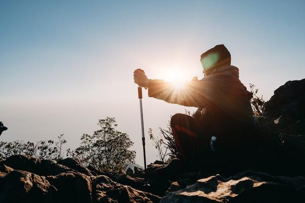 旅行ライフスタイルアドベンチャーコンセプトの夕日シルエット山で男をハイキングします。 Premium写真