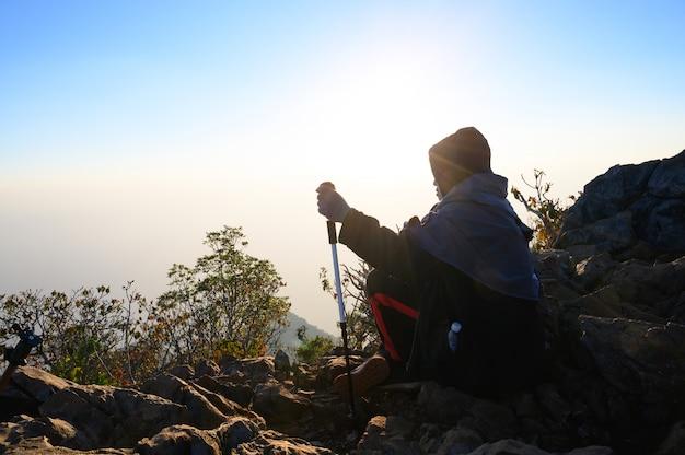 旅行ライフスタイルアドベンチャーの概念と夕焼けシルエット山で丘の上に座っているハイキング男。 Premium写真