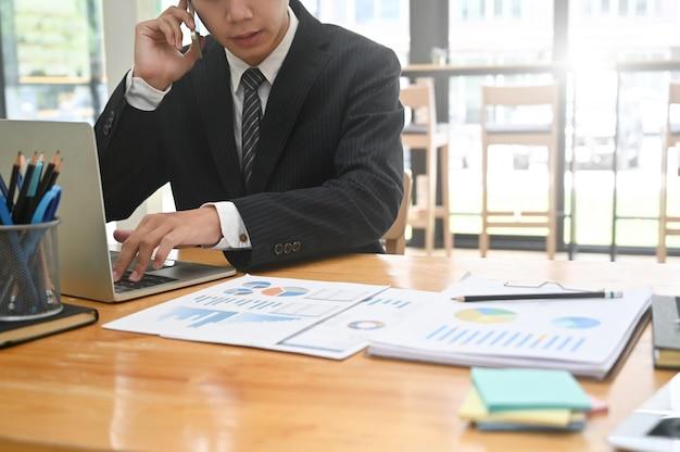 Подрезанный бизнесмен съемки вызывая телефон и используя портативный компьютер на столе офиса. Premium Фотографии