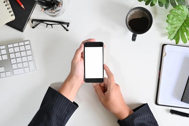 トップビューの実業家が事務机の上のモックアップのスマートフォンを使用して手します。 Premium写真