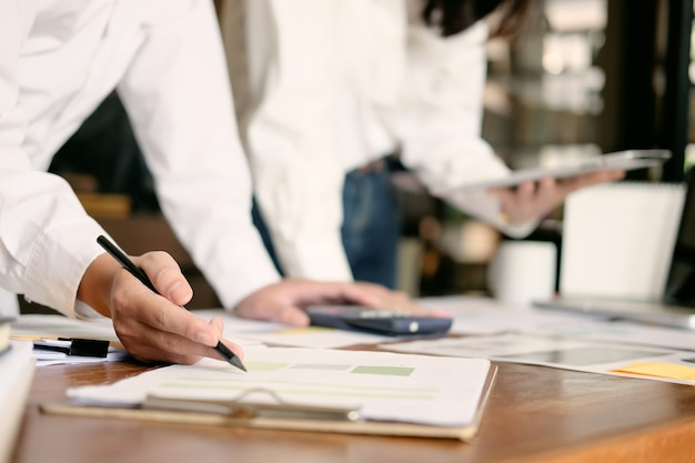 Бизнес-группа, работающая с финансовыми бумажными данными на офисном столе со старинным тоном. Premium Фотографии