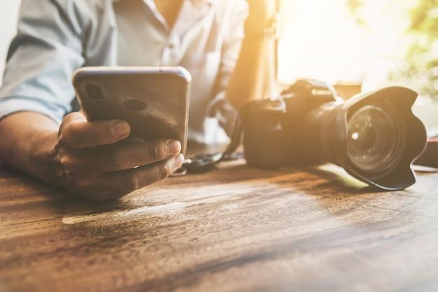 Человек, используя смартфон мобильный телефон для связи с друзьями в кафе Premium Фотографии