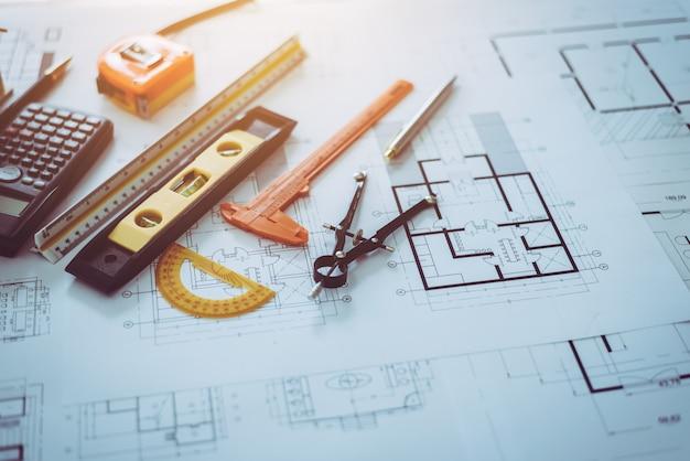 テーブルデスクに置かれた建築家図面計画オブジェクト。 Premium写真