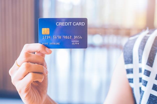ビジネスの女性の手は青いクレジットカードを保持しています。 Premium写真