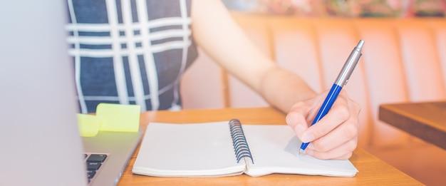 Рука женщины работая на компьютере и писать на блокноте с ручкой в офисе. веб-баннер. Premium Фотографии