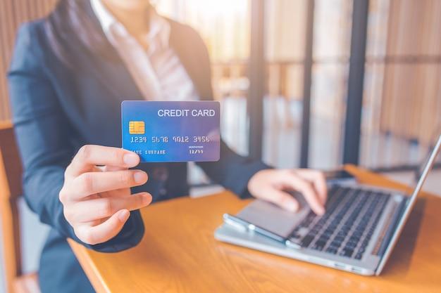 実業家の手は青いクレジットカードを保持しています。ラップトップコンピューターを使用しています Premium写真