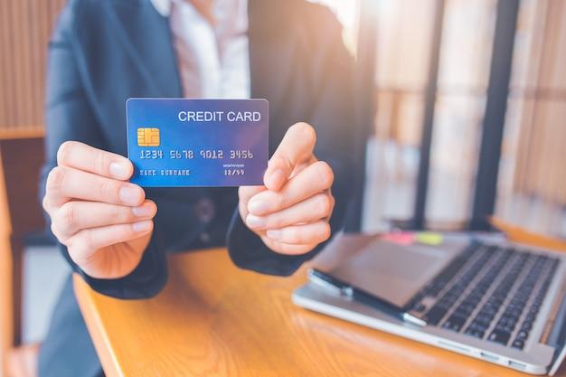 実業家の手は青いクレジットカードを保持します。 Premium写真