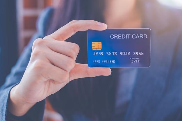 青いクレジットカードを示すビジネス女性 Premium写真
