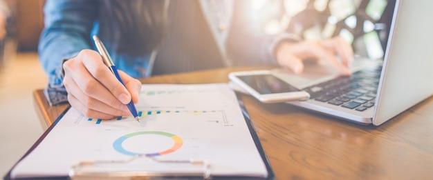 女性の手がチャートやグラフを書く結果をペンで表示します。ウェブバナー。 Premium写真