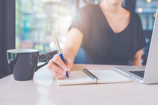 ビジネスの女性の手はペンでノートに書いています。 Premium写真