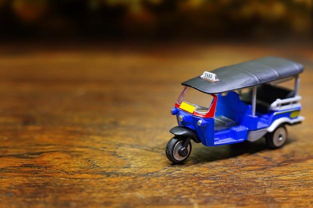 木のテーブルにトゥクトゥクタクシーのおもちゃ Premium写真