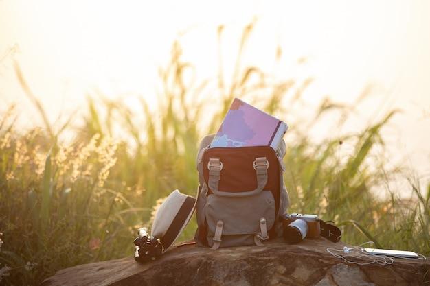 Карта в рюкзаке, мобильный телефон с наушником и шляпой на горе с путешественником. Premium Фотографии