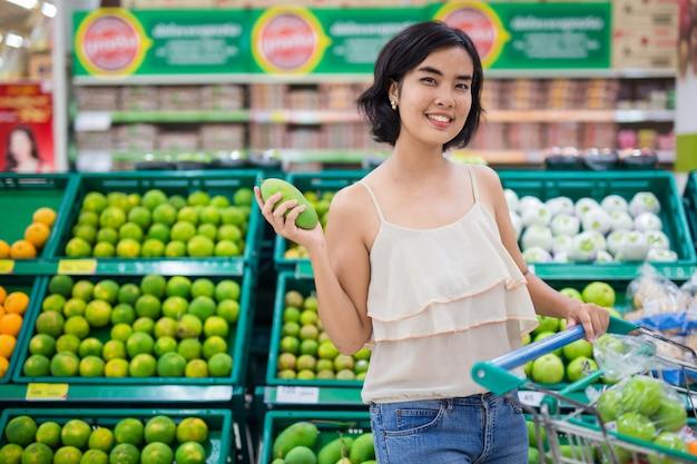 アジアの女性はスーパーマーケットの果物と野菜を買っています。 Premium写真