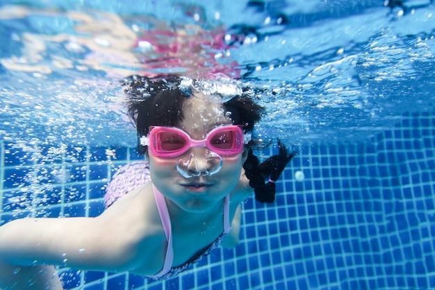 水泳と青いプールでのダイビングの女の子 Premium写真