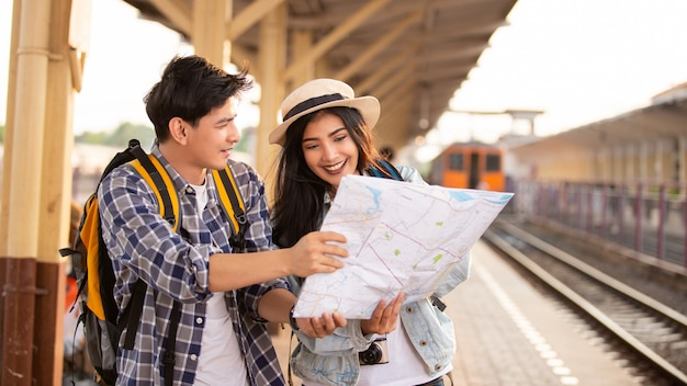 Азиатские туристы с рюкзаками с помощью карты на вокзале Premium Фотографии