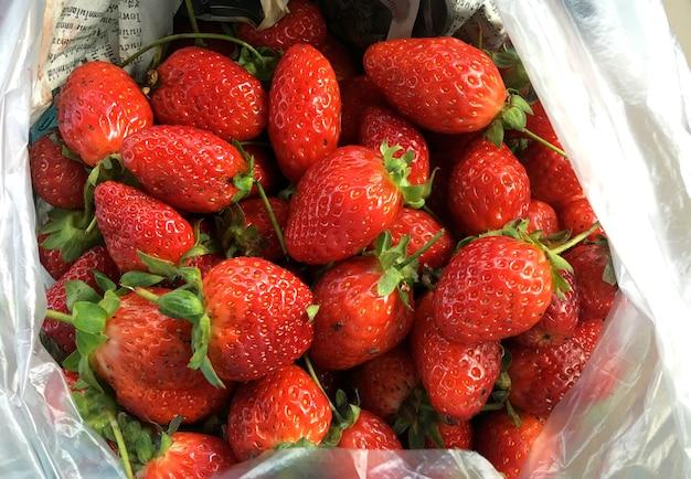 新鮮なイチゴの背景。クローズアップで熟したイチゴ。 Premium写真