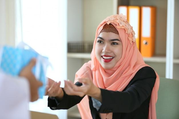 イスラム教徒の女性は現在の贈り物を得る Premium写真