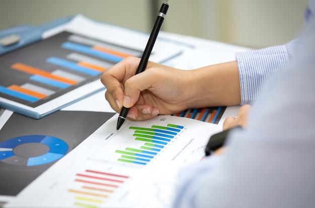 Вид сбоку деловых людей, пишущих на документы на столе Premium Фотографии