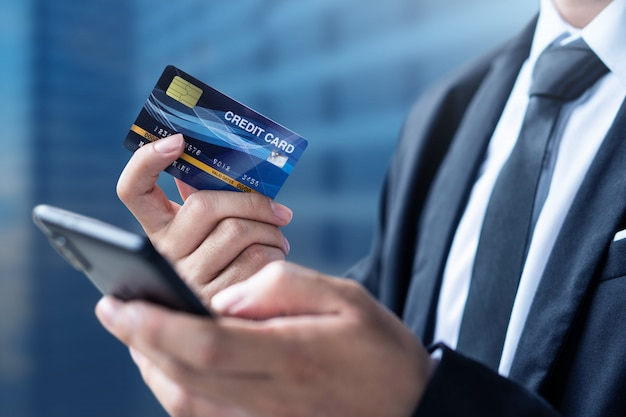 ビジネスマンの支払いやスマートフォンとクレジットカードでの買い物 Premium写真