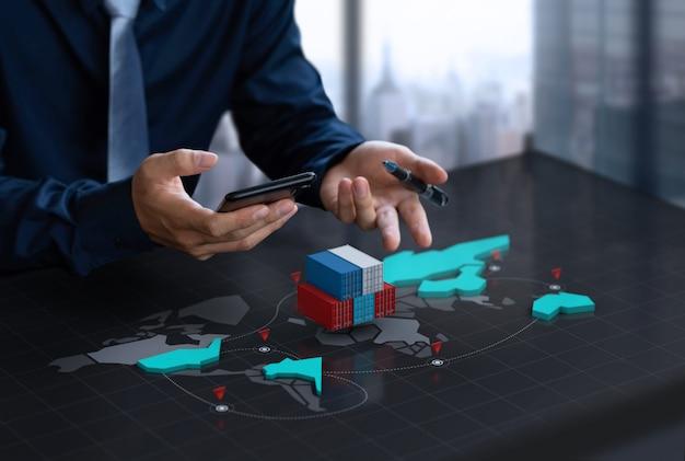 ビジネスマンは、デジタル世界地図画面でエクスポートコンテナーを表示します Premium写真