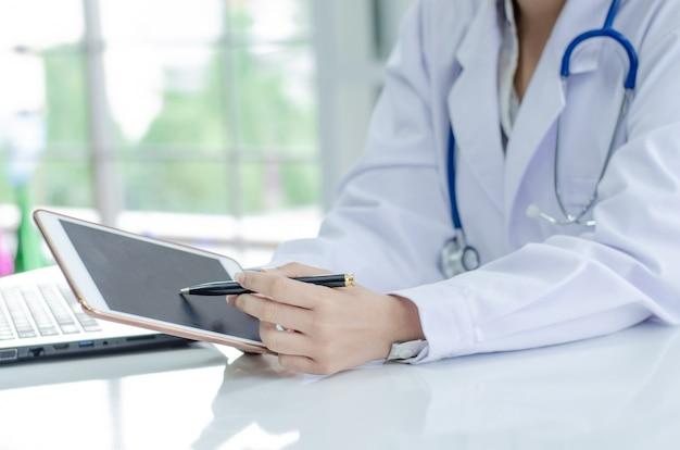 医者のラップトップコンピューターでの作業、書類に書いています。病院の背景 Premium写真