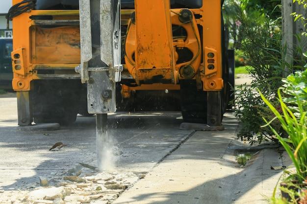 コンクリートの路面を壊すショベル Premium写真