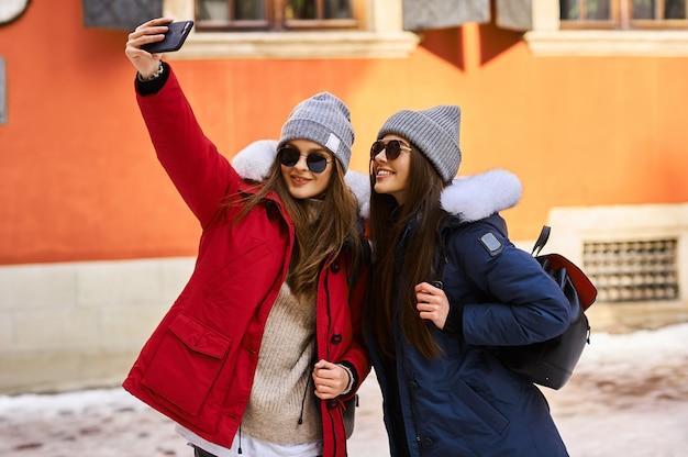 トレンディな若い女の子がクリスマスタイムに街に飛び込んで楽しんで Premium写真