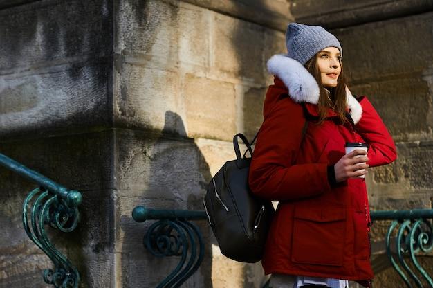 冬時間で路上でコーヒーを飲む若いおしゃれな女の子の肖像画 Premium写真