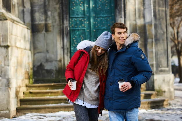 トレンディな若いカップルはクリスマスに街を歩く Premium写真