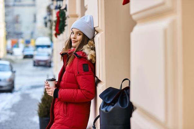 冬時間で街の通りを歩いてファッショナブルな少女の肖像画 Premium写真