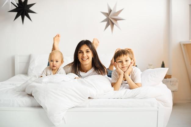 幸せな愛情のある家族。寝室で彼女の子供たちと遊ぶ母 Premium写真