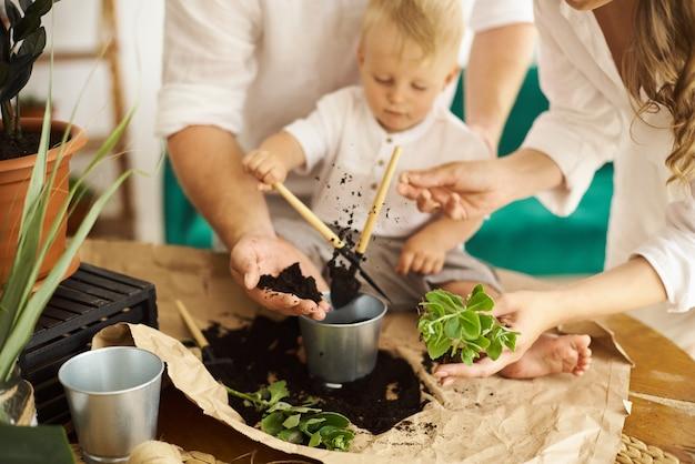 Счастливая семья работает дома. пересадка растений с ребенком Premium Фотографии